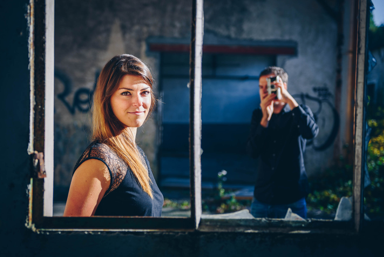 photo en couleur représentant un jeune couple en train de se photographier dans une usine abandonnée auteur Franck Burjes photographe de portrait à Amiens
