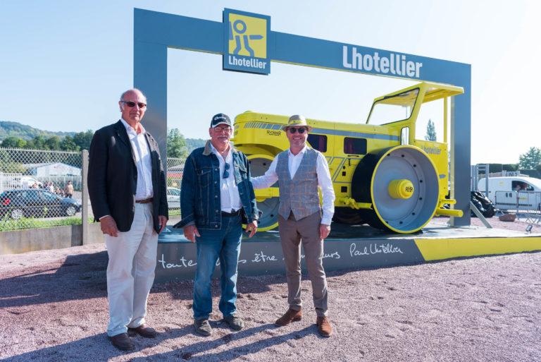 photo en couleur représentant Paul Lhotellier et son père accompagnés d'un ancien salarié devant une vieille machine de travaux publics pendant la fête des 100 ans auteur Franck Burjes photographe de reportage à Amiens